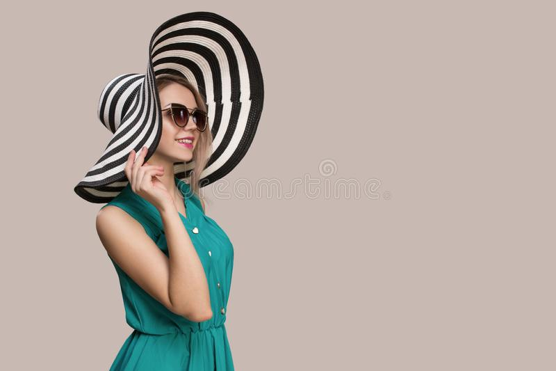 Muchacha de la moda en un sombrero grande y gafas de sol en un fondo coloreado fotografía de archivo