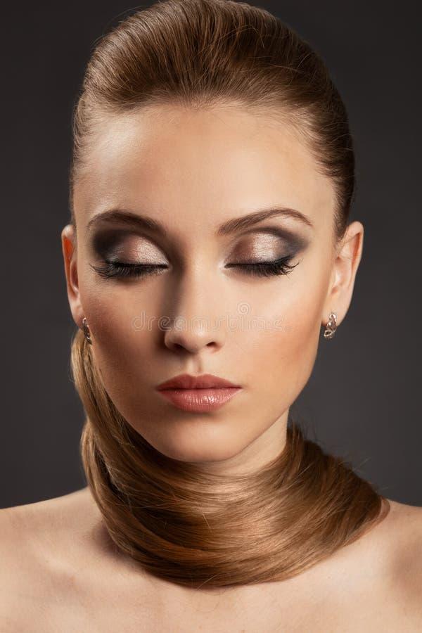 Muchacha de la moda. Maquillaje brillante y pelo sano foto de archivo