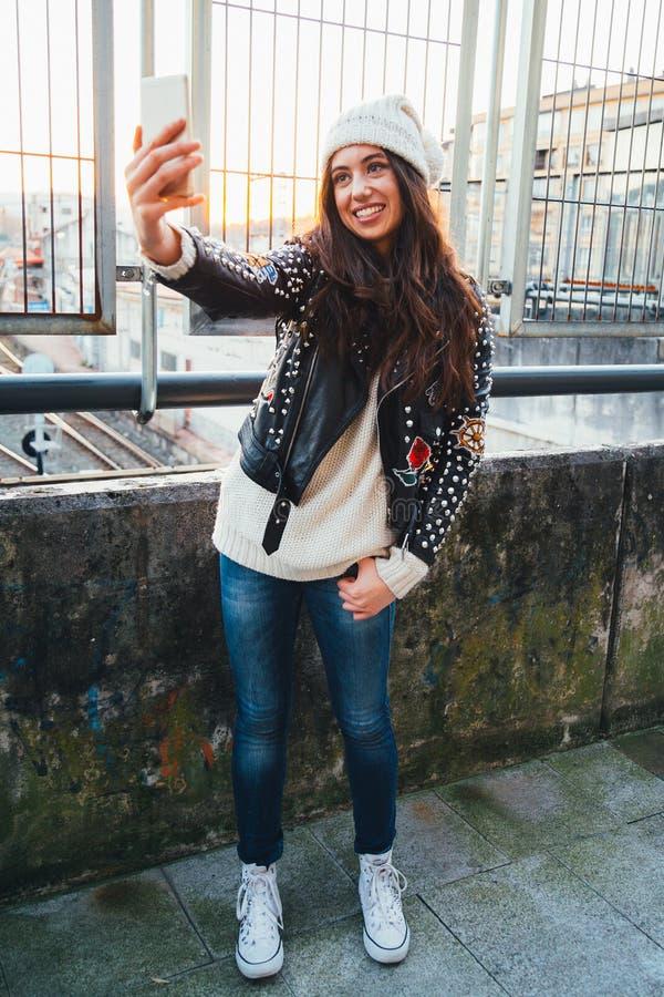 Muchacha de la moda de Selfie en la ciudad en la puesta del sol imagen de archivo libre de regalías