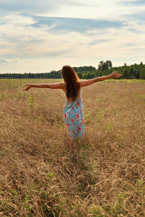Muchacha de la mujer joven que se coloca con ella detrás con los brazos abiertos a la puesta del sol en un campo de trigo en el c imágenes de archivo libres de regalías