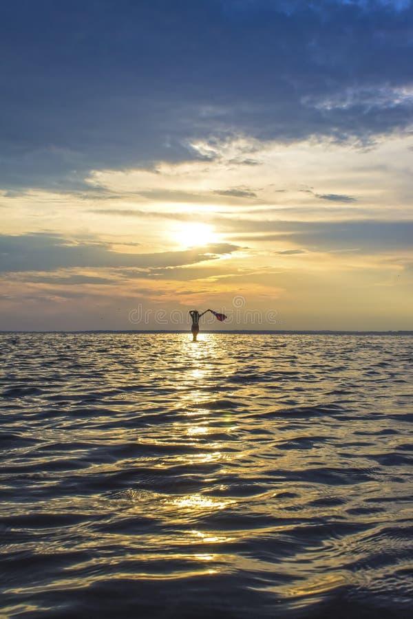 Muchacha de la mujer que camina en el mar en la puesta del sol, amanecer fotografía de archivo
