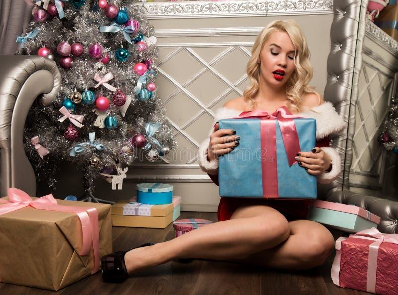 Muchacha de la Navidad con los regalos cerca del árbol de navidad Mujer vestida como Santa fotografía de archivo