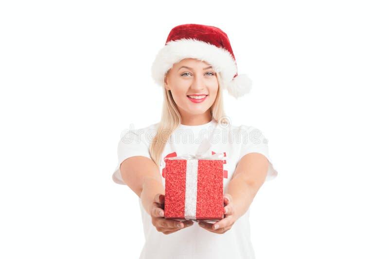muchacha de la Navidad en sombrero del ` s de Papá Noel con el regalo foto de archivo