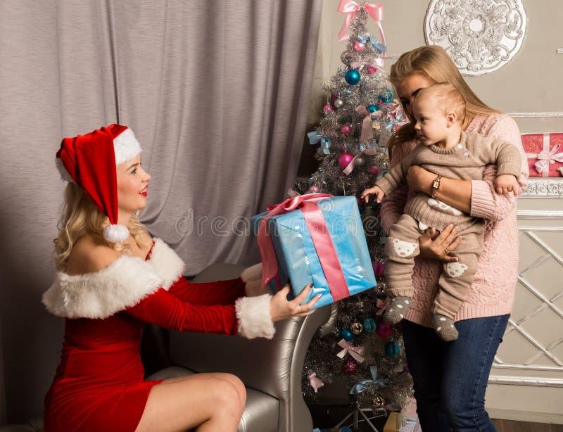 Muchacha de la Navidad que da presentes al pequeño bebé Mujer vestida como Papá Noel imagenes de archivo