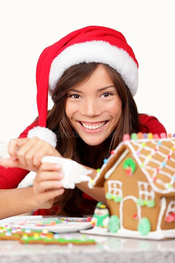 Muchacha de la Navidad que hace la casa de pan de jengibre foto de archivo libre de regalías