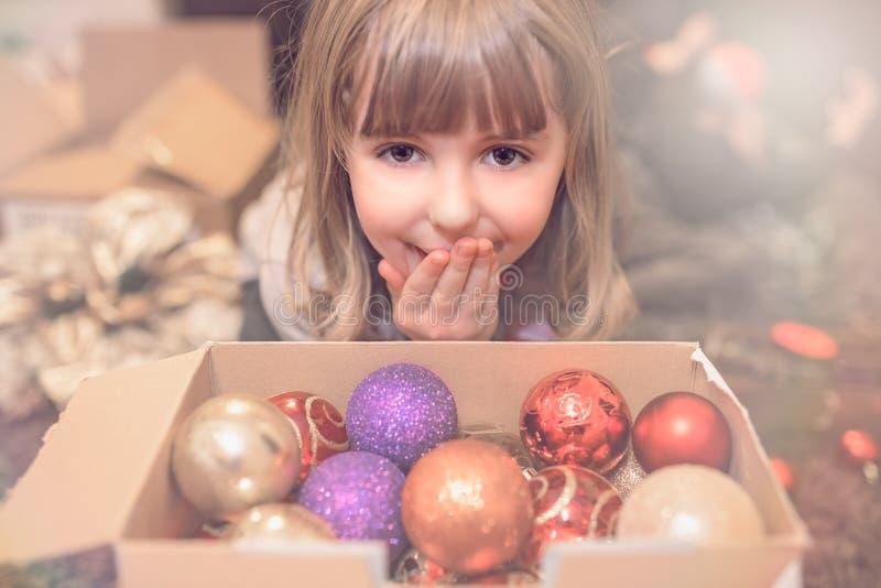 Muchacha de la Navidad que mira el retrato de las decoraciones foto de archivo