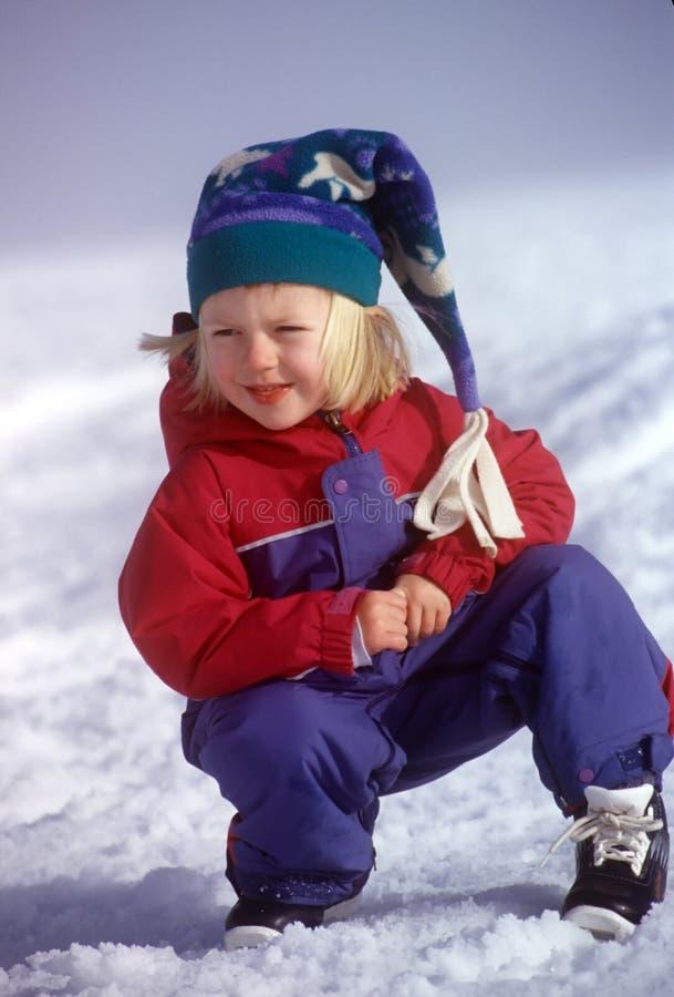 Muchacha de la nieve en Snowsuit y casquillo foto de archivo