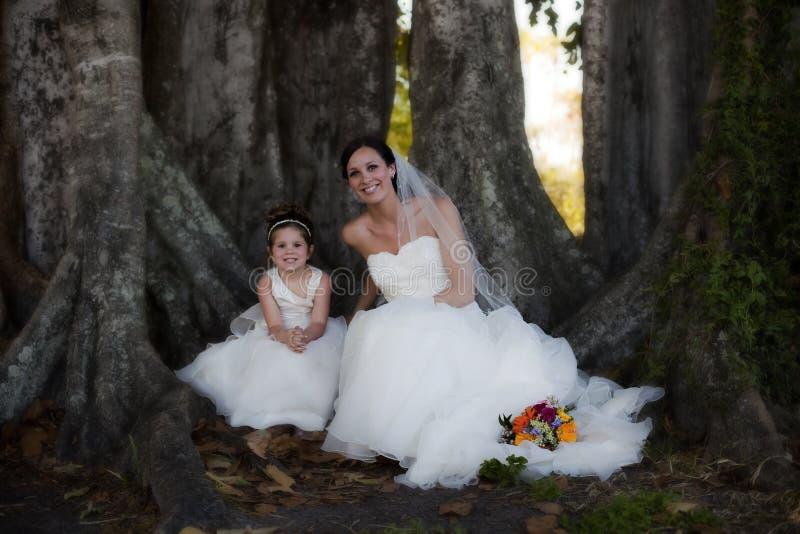 Muchacha de la novia y de flor bajo árbol imagenes de archivo