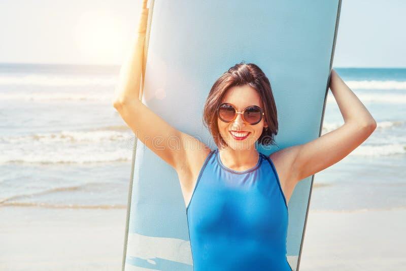 Muchacha de la persona que practica surf en gafas de sol grandes con el tablero largo que presenta en la playa del oc?ano Imagen  fotos de archivo libres de regalías