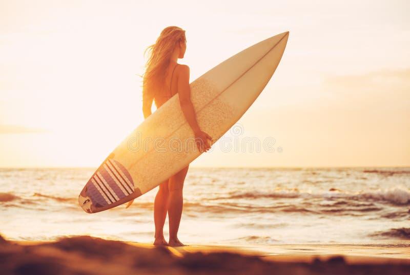 Muchacha de la persona que practica surf en la playa en la puesta del sol fotos de archivo