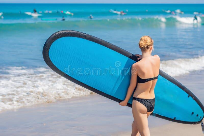 Muchacha de la persona que practica surf en la playa arenosa Muchacha de la persona que practica surf Wom joven hermoso fotografía de archivo