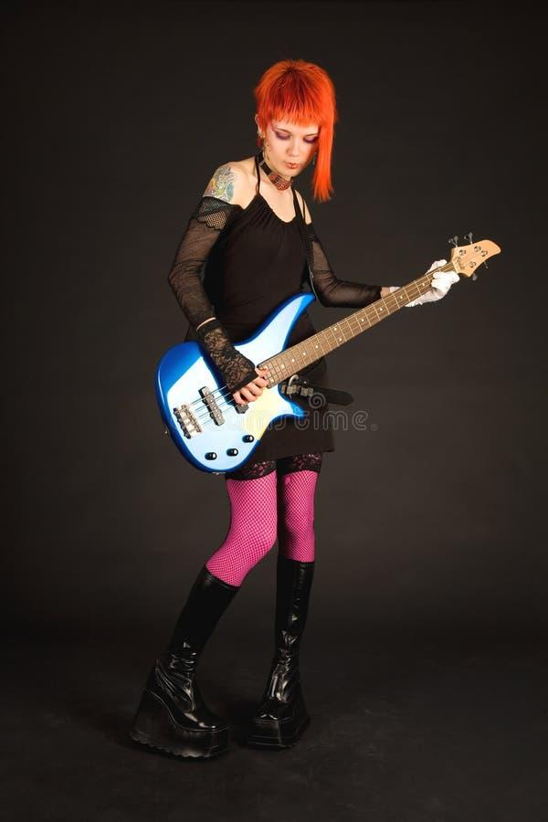 Muchacha de la roca que toca la guitarra baja fotografía de archivo