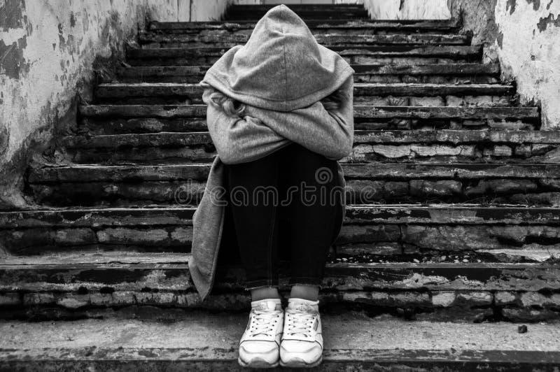 Muchacha de la tristeza que se sienta en las escaleras foto de archivo libre de regalías