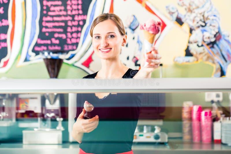 Muchacha de las ventas que da la oblea del helado sobre contador fotografía de archivo libre de regalías