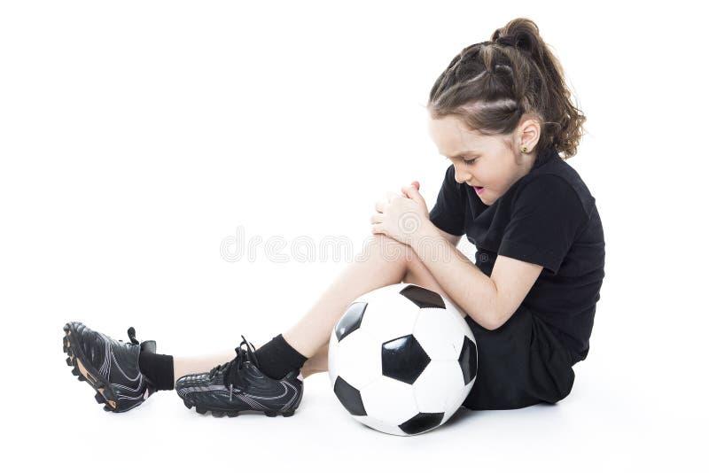 Muchacha de lesión con el balón de fútbol aislado en blanco foto de archivo