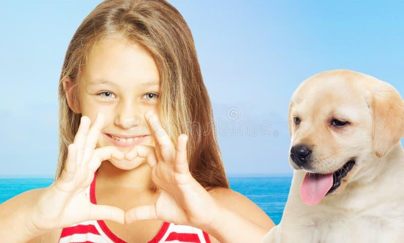 Muchacha de Llittle que muestra las manos del corazón y el perrito de Labrador imagen de archivo libre de regalías