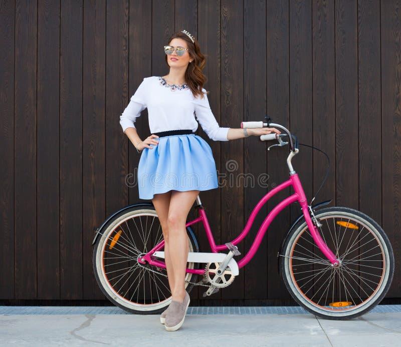 Muchacha de moda de moda con la bici del vintage en fondo de madera Foto entonada Concepto moderno de la forma de vida de la juve fotografía de archivo