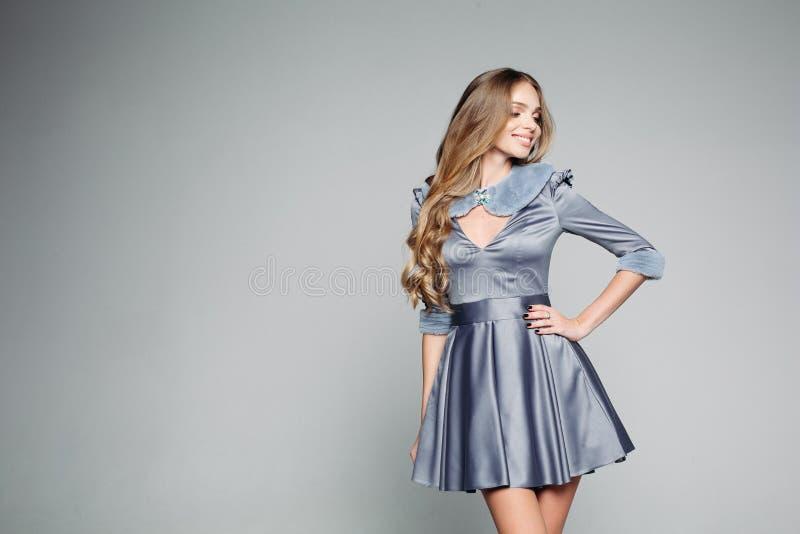 Muchacha de moda del blondie en el vestido gris dtylish que presenta en estudio foto de archivo