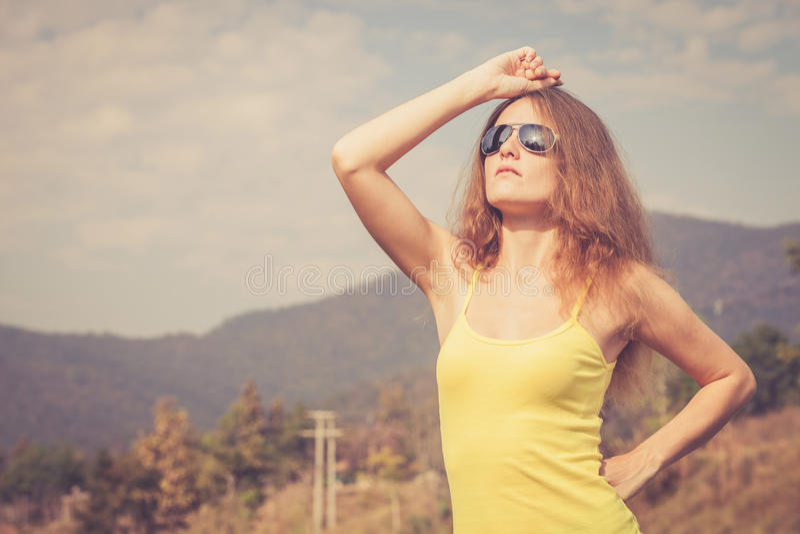 Muchacha de moda del inconformista en las gafas de sol que se relajan en el camino en el th foto de archivo libre de regalías