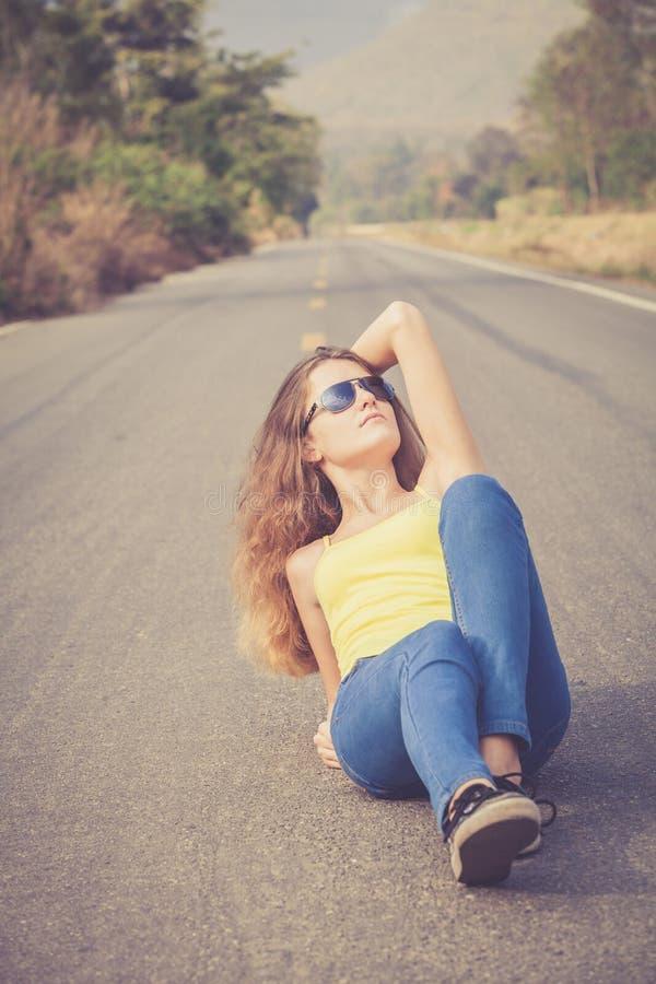 Muchacha de moda del inconformista en las gafas de sol que se relajan en el camino en el th imagen de archivo libre de regalías