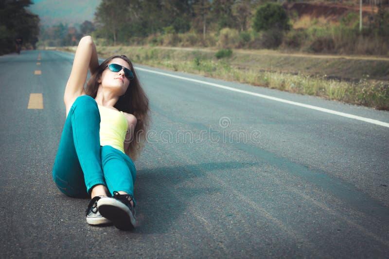 Muchacha de moda del inconformista en las gafas de sol que se relajan en el camino en el th imágenes de archivo libres de regalías