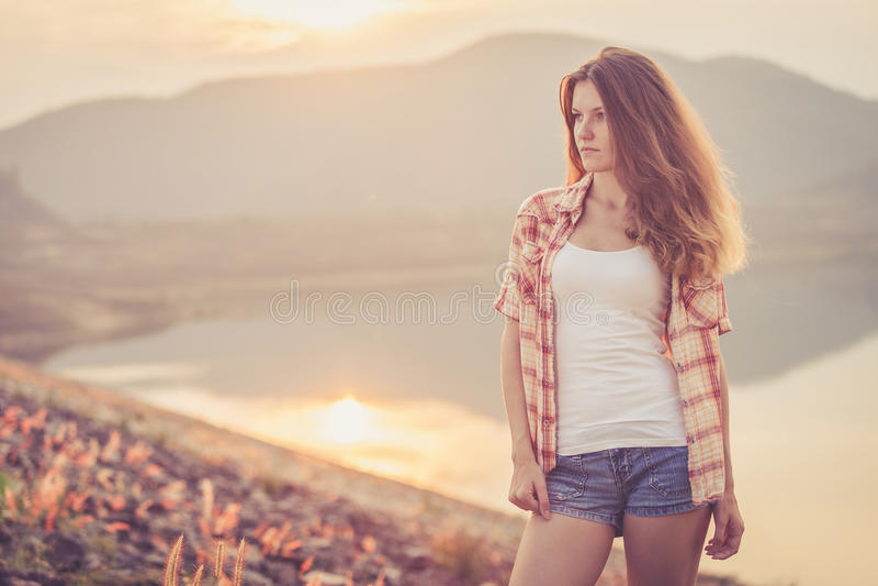 Muchacha de moda del inconformista que se relaja cerca del lago en el tiempo del día fotografía de archivo libre de regalías