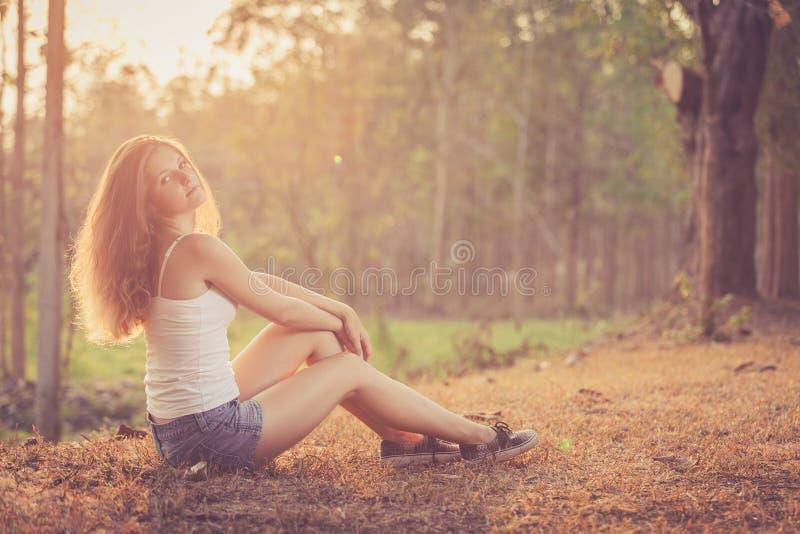 Muchacha de moda del inconformista que se relaja en el camino en el tiempo del día imagenes de archivo