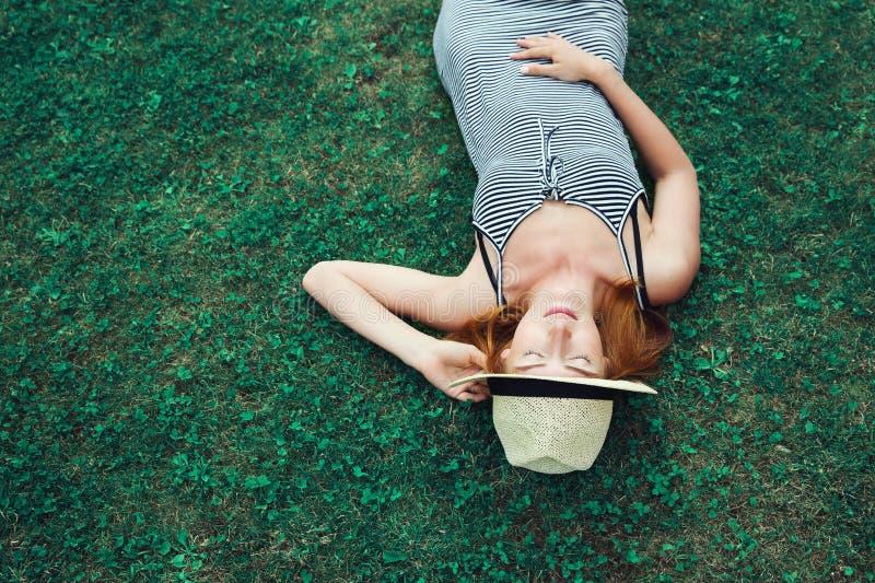 Muchacha de moda del inconformista que se relaja en la hierba imágenes de archivo libres de regalías