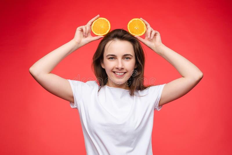 Muchacha de moda divertida con el peinado que sostiene naranjas en ojos foto de archivo