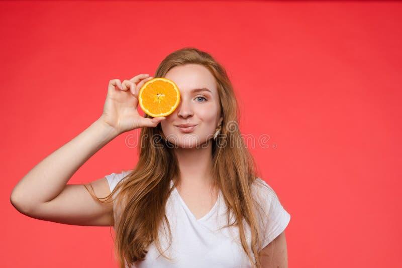 Muchacha de moda divertida con el peinado que sostiene naranjas en ojos imagenes de archivo