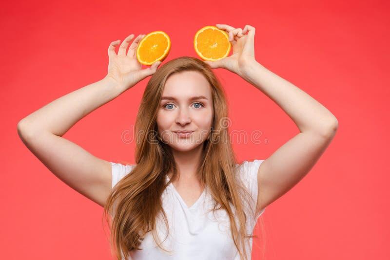 Muchacha de moda divertida con el peinado que sostiene naranjas en ojos fotos de archivo