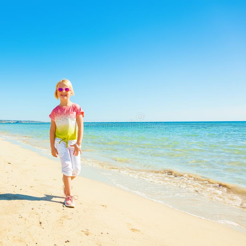 Muchacha de moda feliz en camisa colorida en caminar de la costa foto de archivo