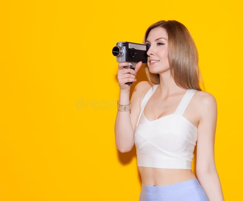 Muchacha de moda hermosa que presenta y que sostiene una cámara de película del vintage en un top y una falda en un fondo amarill fotos de archivo