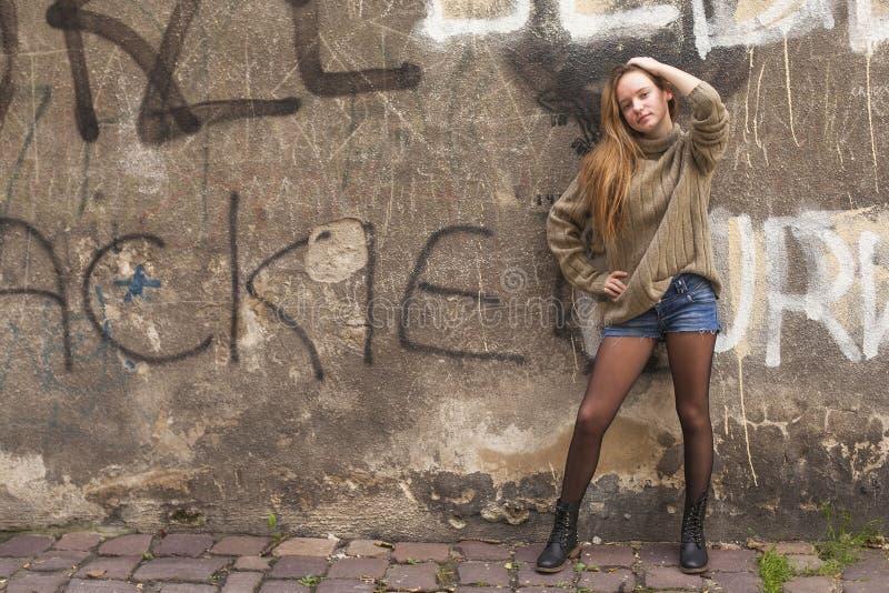 Muchacha de moda joven que presenta cerca de la pared vieja imagen de archivo