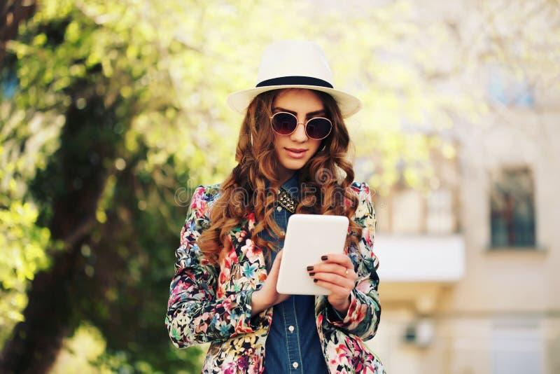 Muchacha de moda joven sonriente del inconformista en fondo de la ciudad en la luz del sol al aire libre foto de archivo libre de regalías