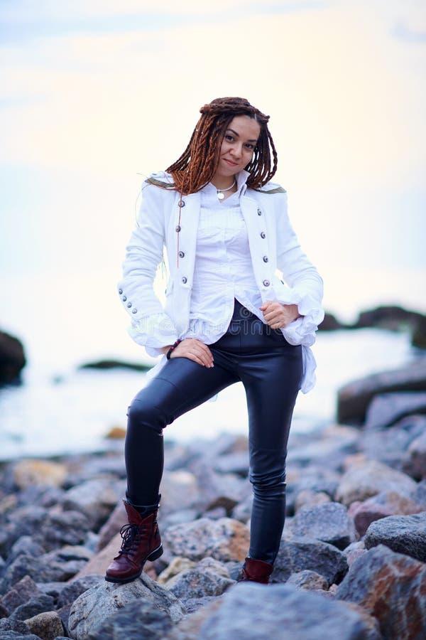Muchacha de moda de los Dreadlocks vestida en la chaqueta blanca y los pantalones de cuero negros que presentan cerca del mar por foto de archivo libre de regalías