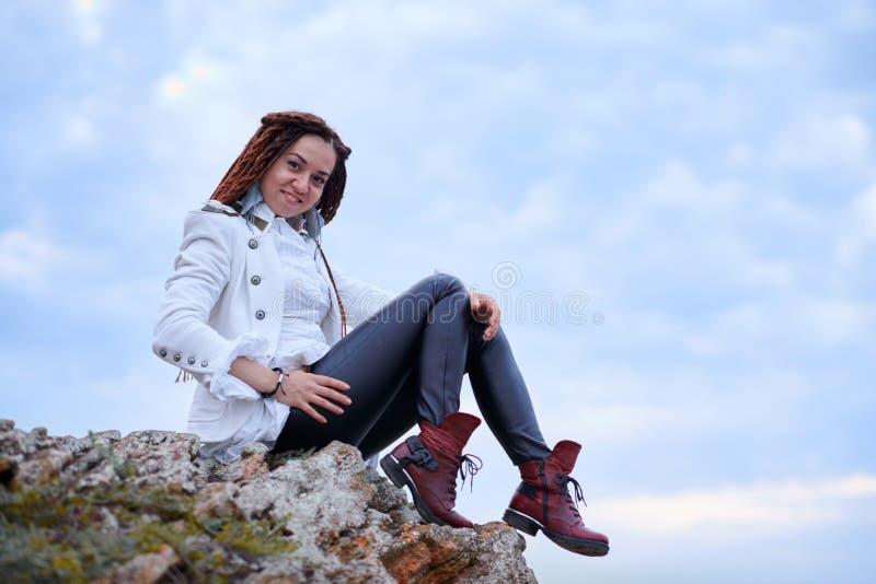 Muchacha de moda de los Dreadlocks vestida en la chaqueta blanca y los pantalones de cuero negros que presentan cerca del mar por fotos de archivo
