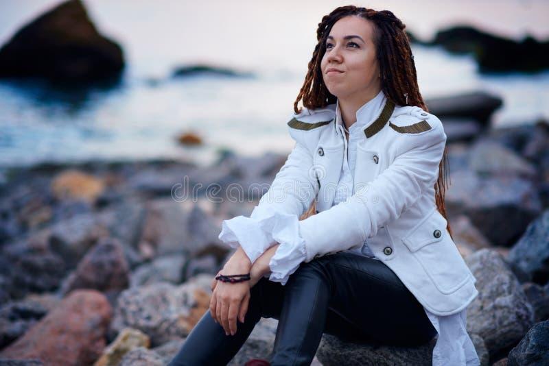 Muchacha de moda de los Dreadlocks vestida en la chaqueta blanca y los pantalones de cuero negros que presentan cerca del mar por imagen de archivo