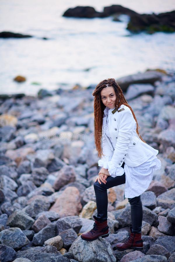 Muchacha de moda de los Dreadlocks vestida en la chaqueta blanca y los pantalones de cuero negros que presentan cerca del mar por imágenes de archivo libres de regalías