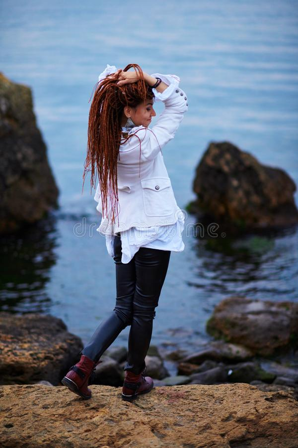 Muchacha de moda de los Dreadlocks vestida en la chaqueta blanca y los pantalones de cuero negros que presentan cerca del mar por foto de archivo