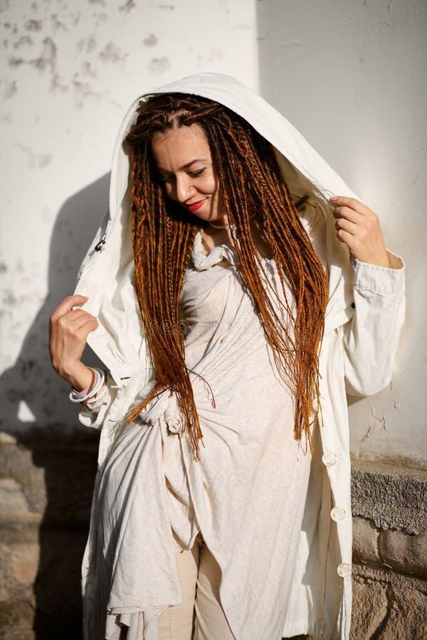 Muchacha de moda de los Dreadlocks vestida en la presentaci?n blanca en luz del sol brillante fotografía de archivo