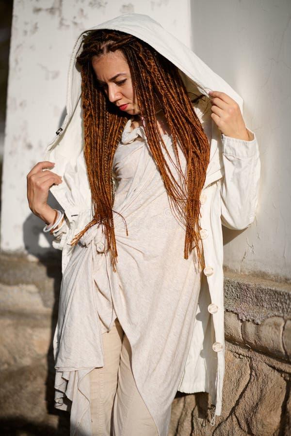 Muchacha de moda de los Dreadlocks vestida en la presentaci?n blanca en luz del sol brillante foto de archivo libre de regalías