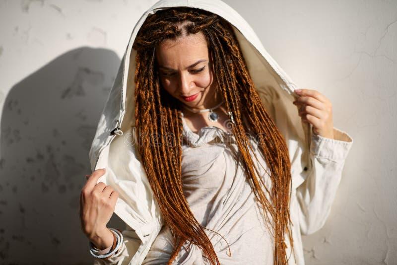 Muchacha de moda de los Dreadlocks vestida en la presentaci?n blanca en luz del sol brillante fotos de archivo