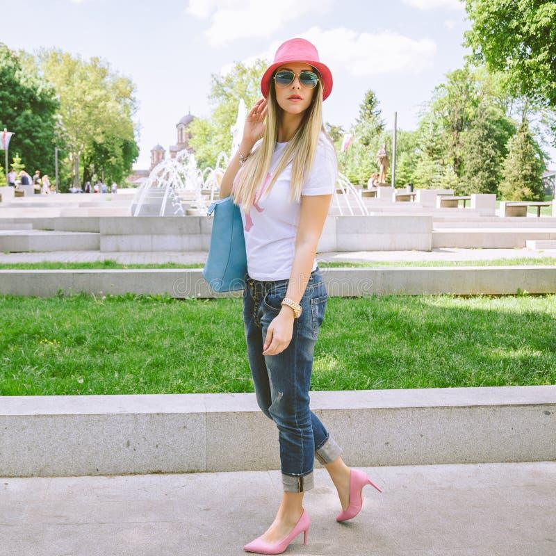 Muchacha de moda que presenta en parque foto de archivo