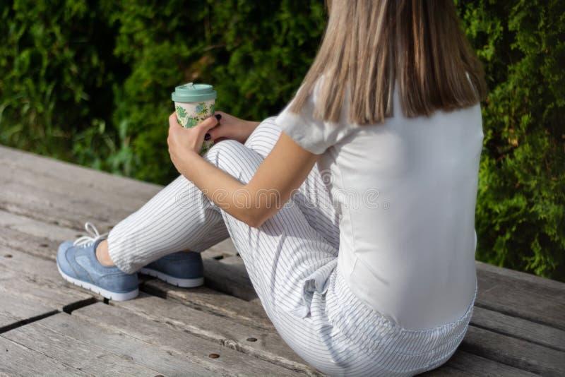 Muchacha de moda que se sienta en banco con los pantalones rayados y que sostiene la taza de café Mujer que descansa en el parque imagenes de archivo