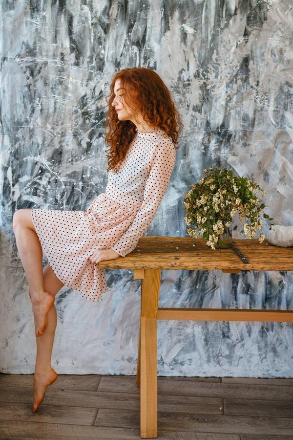 Muchacha de moda que se sienta en la tabla, pelo rojo foto de archivo