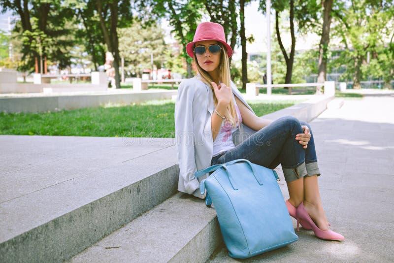 Muchacha de moda que se sienta en las escaleras en parque fotografía de archivo libre de regalías