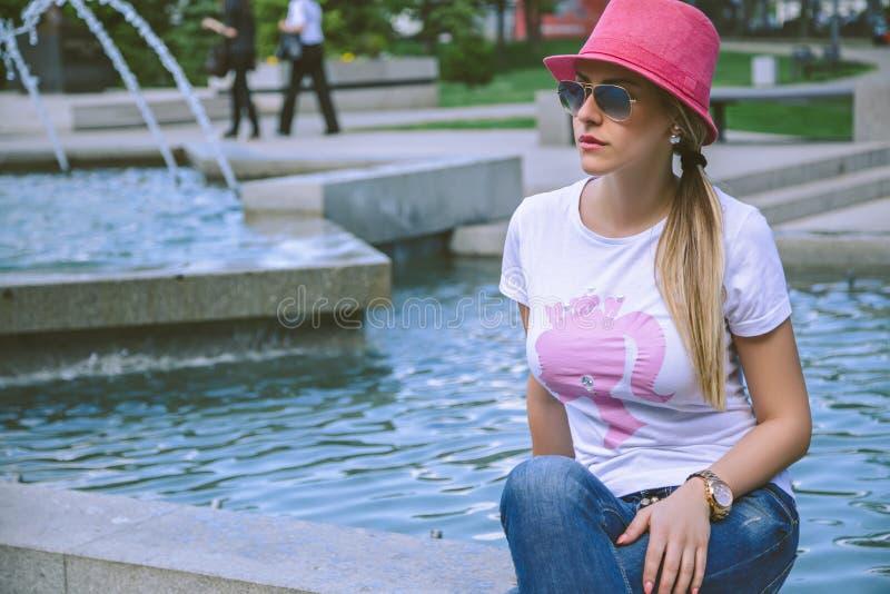 Muchacha de moda que se sienta por la fuente foto de archivo libre de regalías