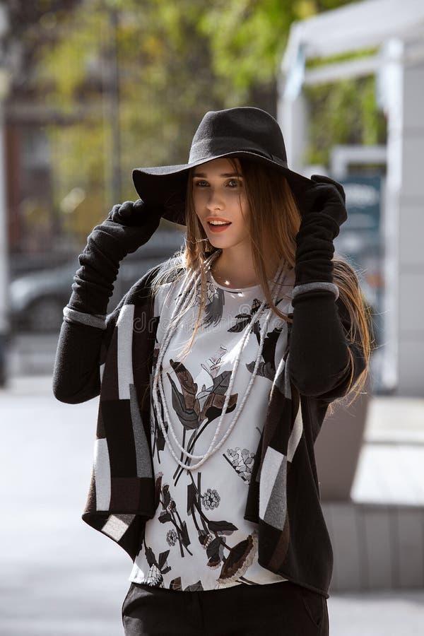 Muchacha de moda vestida en pantalones negros, una camisa gris elegante y suéter y en un sombrero negro con los paseos anchos del fotografía de archivo libre de regalías