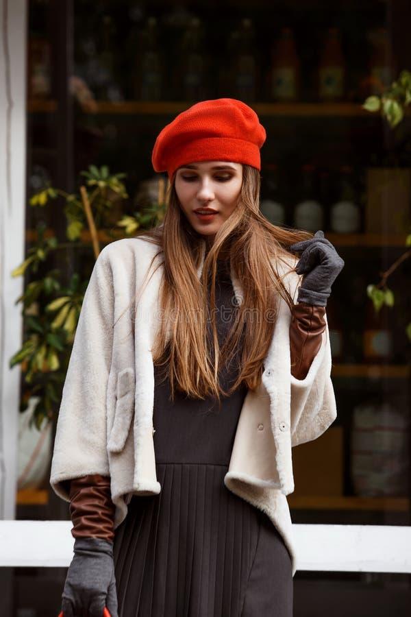 Muchacha de moda vestida en vestido gris elegante, capa de zalea corta, guantes y paseos rojos de la boina en el parque en imagen de archivo